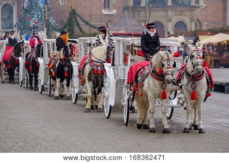 Krakow, Poland - December 19, 2016: Carriages for riding tourists on the background of Mariacki cathedral at main square in old city