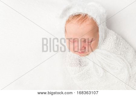 beautiful swaddled newborn baby in white closeup with ears