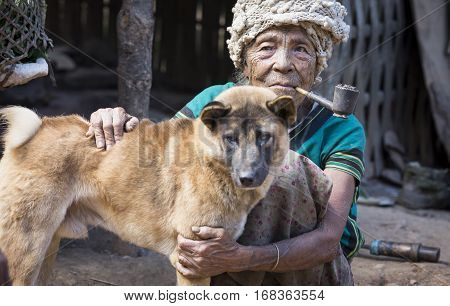 Chin region Myanmar November 11 2014: muun tribe chin lady with her dog
