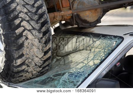 Car wreck with truck tires on windshield of small destruction crash