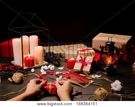 Close-up partial view of female hands packing gift at wooden table with presents and decorations