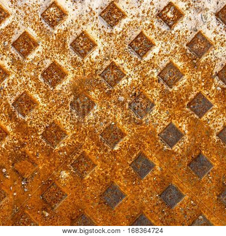 Orange rusted manhole texture with square pattern background macro.