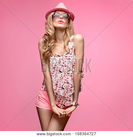 Fashion woman Having Fun Dance. Blond Model Crazy Girl in Stylish Spring Summer Outfit.Fashion Sunglasses, Glamour Pink Shorts, Floral Top.Cheeky Hipster, Trendy pink fashion Hat.Wavy summer Hairstyle