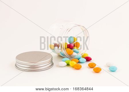 Colored smarties scattered out of an open glass jar isolated on white background. Shallow depth of field.