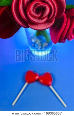 Shot of red fabric roses with two heart-shaped lollipos underneath the flowers.