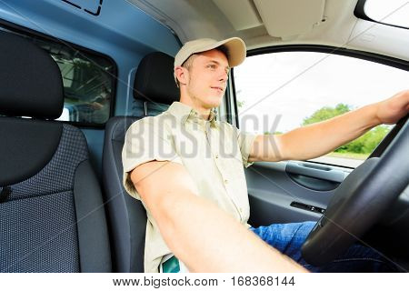 Wide angle shot of a delivery boy driving his van.