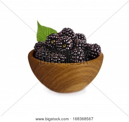 Blackberries on a wooden bowl isolated on white. Ripe blackberries with mint close-up. Background berry. Sweet and juicy blackberries with copy space for text.