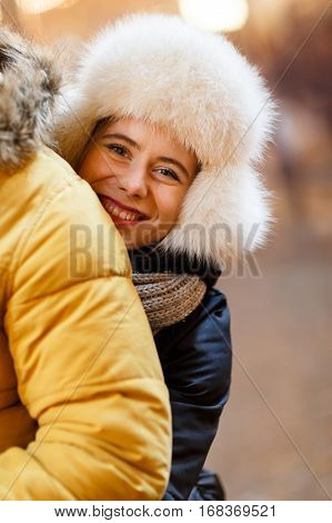 Loving woman hugging beloved man in street in winter