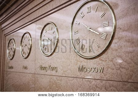 Clocks on wall showing time in London, Paris, Hong Kong and Moscow.