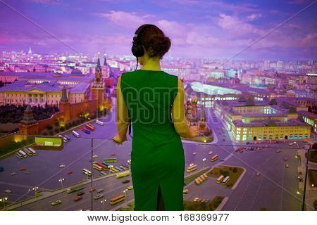 Woman in green dress with headphone looks at diorama of Moscow, rear view.