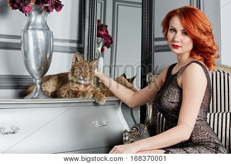 Young red-haired woman sits at table with lying lynx cub.