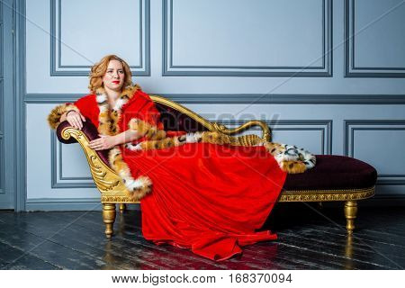 Blonde woman in red dress and cloak lies on couch in room.