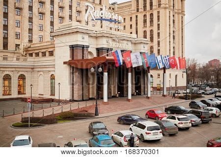 MOSCOW, RUSSIA - NOV 14, 2015: Car parking and central entrance of Radisson Royal Ukraine hotel. Radisson Royal Ukraine hotel is one of seven Stalin skyscrapers.