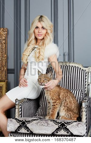 Young blonde woman sits on armrest of armchair on which lynx cub lies.