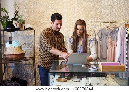 Man and young woman working together in clothes shop