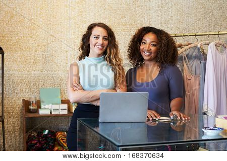 Two women working in clothing store looking to camera