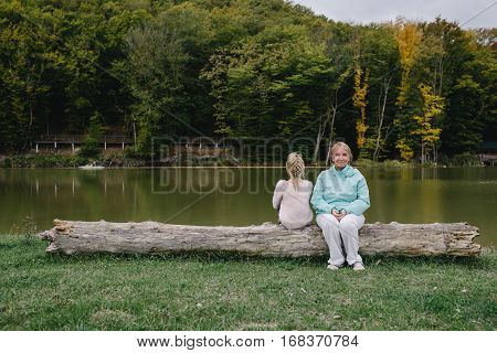 sitting on a log in the background of the lake. conflict of generations. family problems. concept