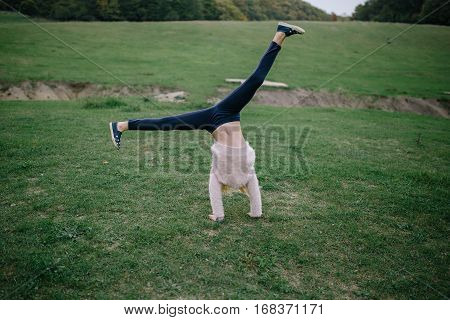 blonde girl performing somersault in park. girl doing exercise outdoors