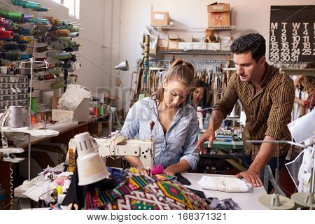 Manager training machinist at a clothing design studio