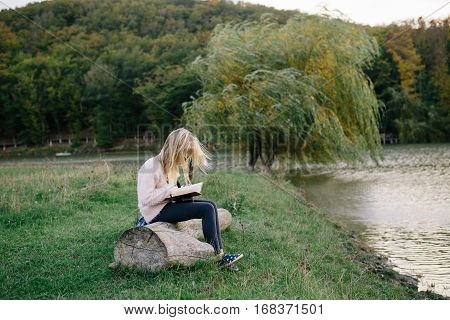little tousled blond girl sitting on a log by the lake and reading a book