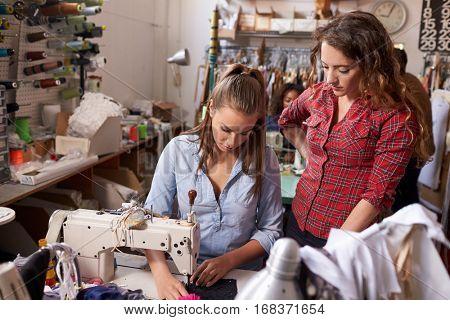 Colleague training machinist at a clothes design studio