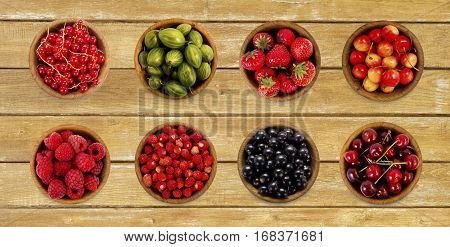 Collage of different fruits and berries on the wooden table. Strawberries currants gooseberry cherries raspberries. Collection of fruits and berries in a bowl. Top view.