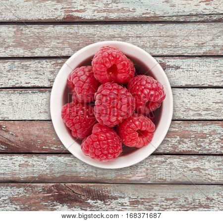 Raspberries in a white ceramic bowl. Ripe and tasty raspberries isolated on a wooden background. Top view.