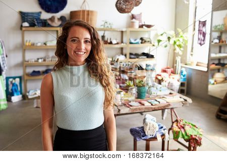 Female sales assistant standing in clothes shop, portrait