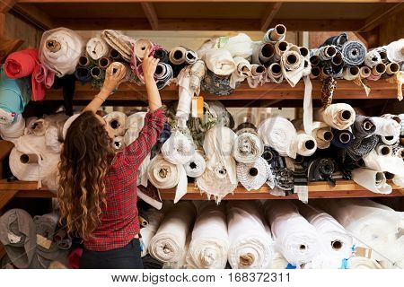 Young woman reaching to select fabric from storage shelves