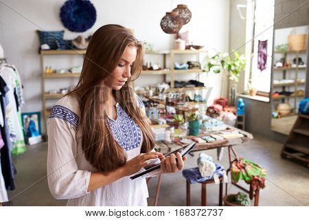 Teenage boutique assistant  using tablet computer in shop