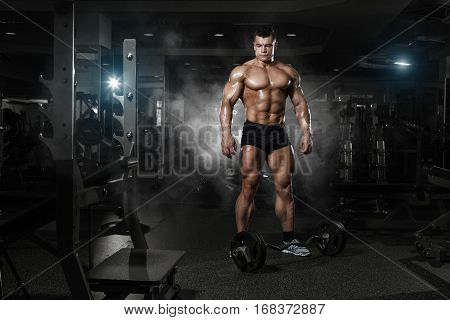 Very Power Athletic Guy Standing With Barbell, Workout In The Gym