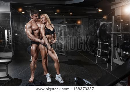 Young sporty beautiful sexy couple huging in gym