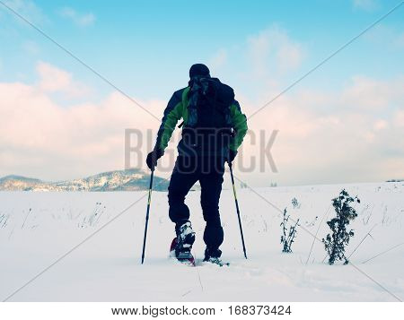 Man With Snowshoes Take A Rest In Snow. Hiker Snowshoeing
