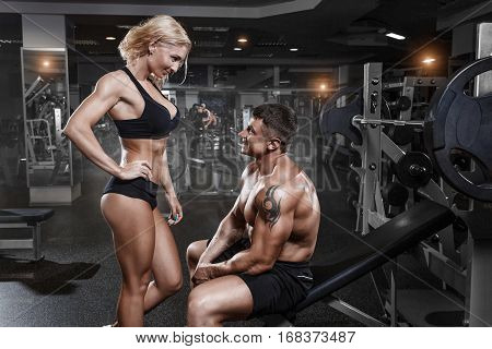 Young sporty beautiful sexy couple training in gym