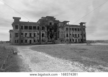 two people look one the big old destroyed building or the house located separately on a glade and against the background of the sky