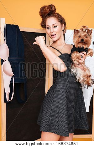 Woman with dog standing near folding screen and pointing away