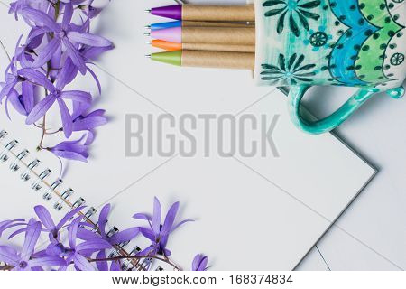 Blank notebook with pen and purple flowers on white wooden background