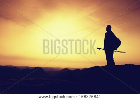 Man In Mountains For A Walk In Evening With Trekking Poles.