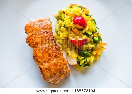 Plate of fried salmon with rice and vegetables