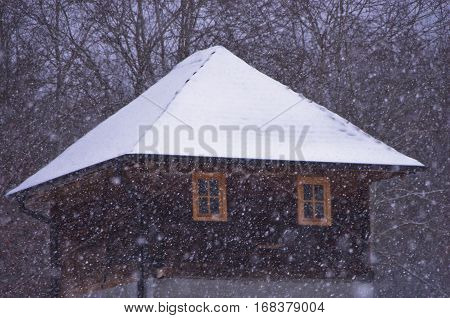 Vintage house with roof covered with snow during snow storm, mountain Kozomor, Serbia