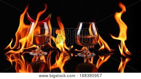 Hot Chili Pepper In A  Brandy Glass With A Fire On A Black Background
