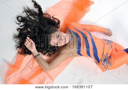 Young beautiful sports girl is resting in the orange suit Lycra
