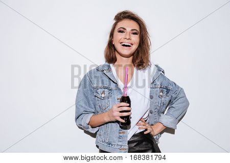 Photo of a young laughing woman dressed in jeans jacket standing isolated over white background while drinking aerated sweet water.