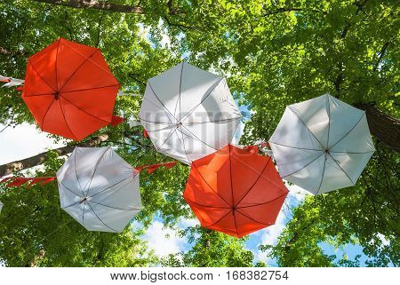 White and red umbrellas over the park against the sky