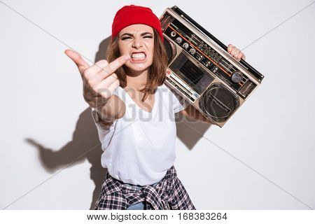 Image of young angry woman dressed in white t-shirt standing isolated over white background while holding tape recorder and showing middle finger to camera.