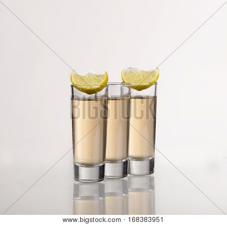 Three Gold Tequila Shots With Lime  On White Background