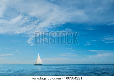 Sailing boat at sea on horizon against blue sky with clouds