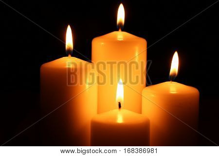 Four big different burning candles. Bright light on dark background. Romantic or RIP darkness template.