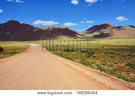 Beautiful landscape of the Namib-Naukluft National Park where the mountains of the Namib desert meet its plains. Dirt road to mountains