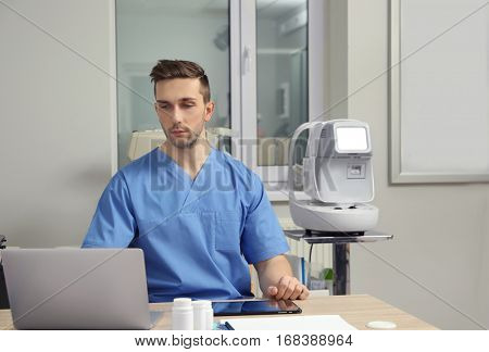 Handsome young ophthalmologist working in office